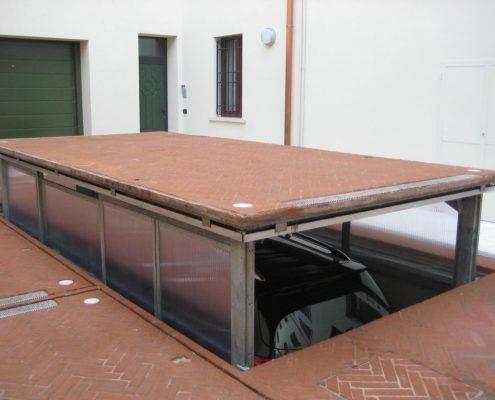 Montauto con cabina in fase di discesa in fossa. Installato in un complesso condominiale