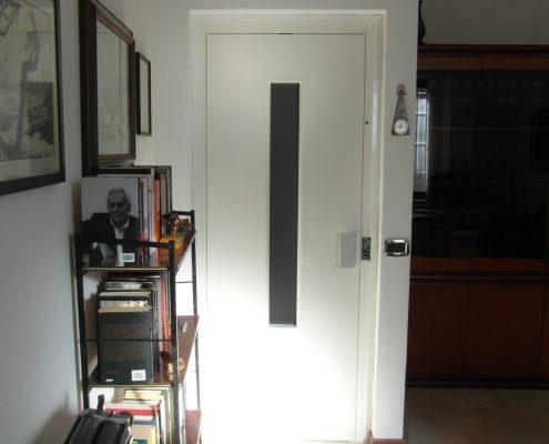Ascensore in casa. Vista porta piano meno uno con vetro da 800 x 100 mm. con fermo porta a 90 gradi.
