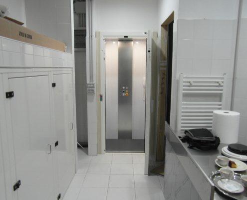 Piattaforma elevatrice Milano. Vista cabina ascensore con porta aperta. Mini ascensore installato a Milano.