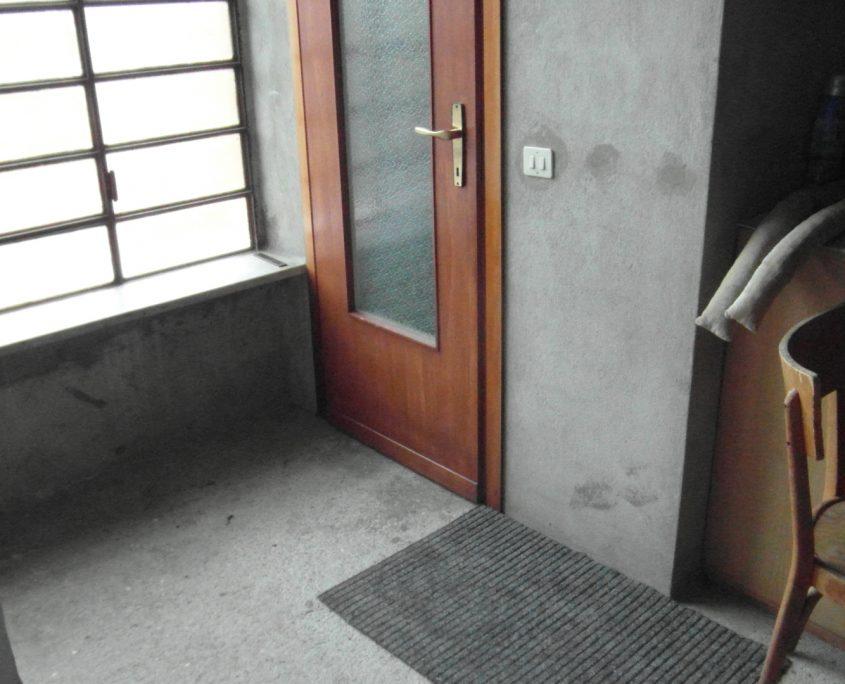 Vista inferiore della porta per accedere al vano scala. Il pavimento è stato rialzato e portato a livello di quello del box.