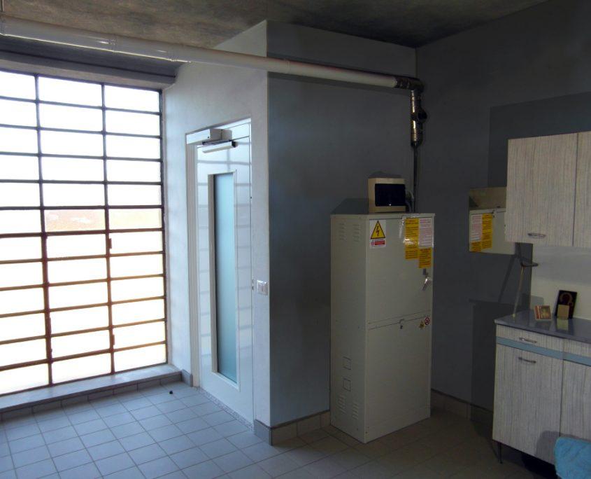 Vista integrale vano ascensore al piano terra con armadio di comando posto sul lato adiacente alla porta.