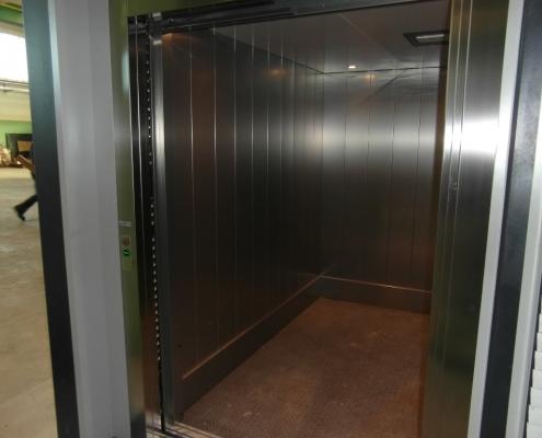 Lato sinistro della cabina e dettaglio della pulsantiera di piano sul telaio della porta.