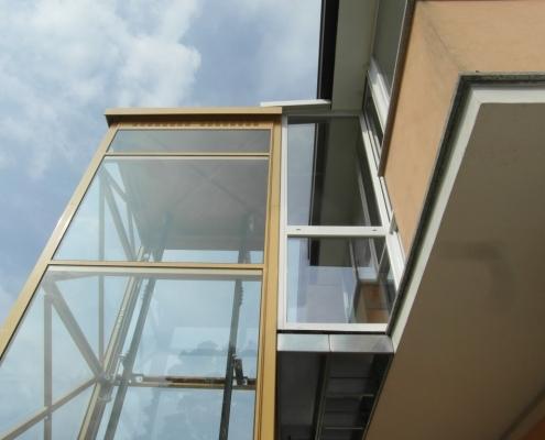 Passerella e serramento che collegano la struttura dell'ascensore al balcone della casa
