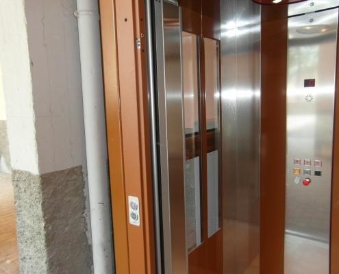 Dettaglio della pulsantiera e della parete sinistra della cabina con inserti in vetro.