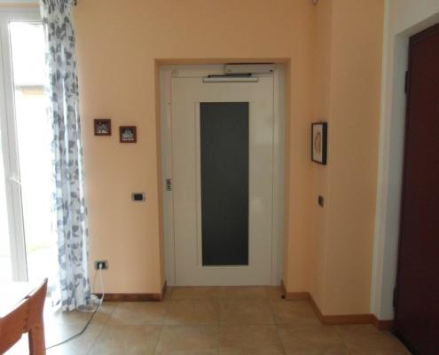 Vista della porta a battente per ascensore al piano terra con vetro da 160 x 50 cm con finitura bianco latte.